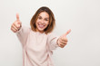 Cheerful woman gesturing thumbs up