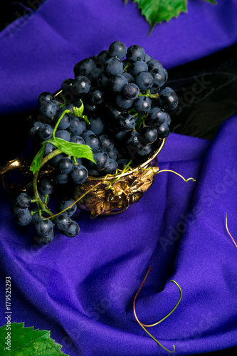Red wine grapes in golden cup on violet background. - 179525293