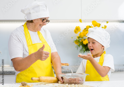 grandmother teaches her grandson to sculpt a dumplings - 179532803