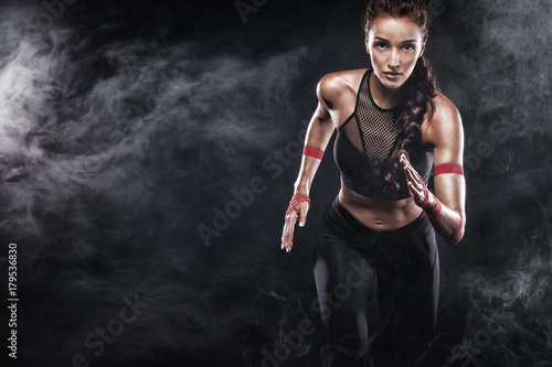 A strong athletic, woman sprinter, running on black background wearing in the sportswear, fitness and sport motivation. Runner concept with copy space.