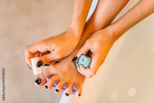 Fotobehang Pedicure Female person hands with nail polish, pedicure