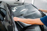 Male specialist with car tinting film in hands