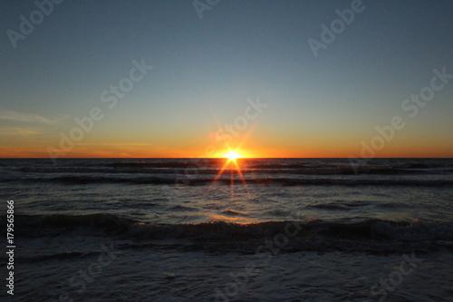 Fotobehang Zee zonsondergang Vibrant Sunset over the ocean water with sun starburst