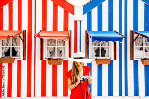Young woman in red dress and sun hat standing on the colorful striped houses bac Poster