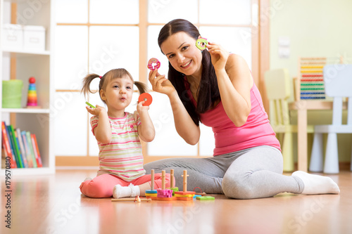 Happy mother and her child playing with colorful logical sorter toy