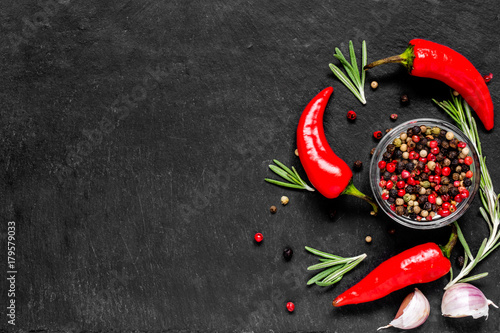 Fotobehang Hot chili peppers Red hot chili peppeprs and peppercorns with rosemary and garlic on black stone background