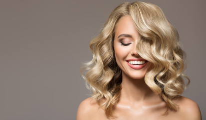 Blonde woman with curly beautiful hair smiling on gray background. © yuriyzhuravov