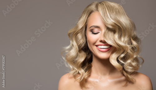 Leinwanddruck Bild Blonde woman with curly beautiful hair smiling on gray background.