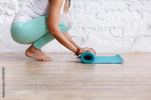 Zakończenie atrakcyjna młoda kobieta składa błękitnego joga lub sprawności fizycznej matę po pracującego w domu w żywym pokoju out. Zdrowe życie, zachowuj kondycję. Poziomy strzał. białe studio na poddaszu