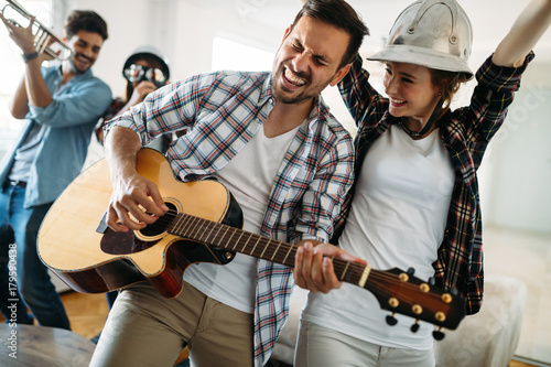 Fotobehang Muziek Cheerful friends having party together and playing instruments