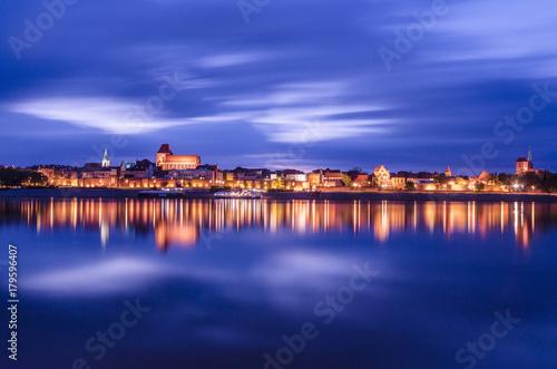 Fototapeta Torun at night. UNESCO-class medieval Old Town reflected in Vistula river, Poland. Europe.