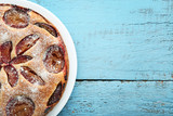 Sweet plum cake on blue wooden table