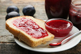 Bread with plum jam on grey wooden table