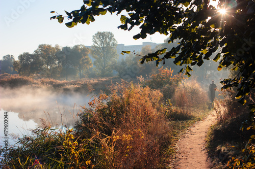 Fotobehang Diepbruine Autumn landscape in city park. Man walking on path along foggy river. Sun shines through leaves