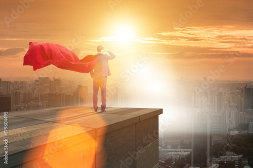 Super hero businessman  on top of building ready for challenge