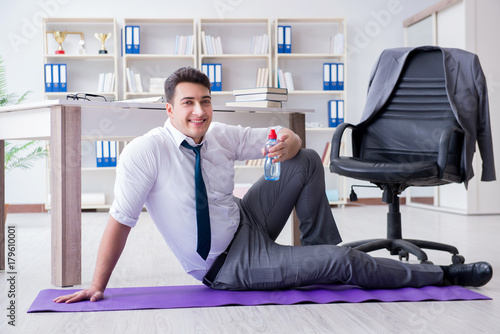 Businessman sitting on the floor drinking water