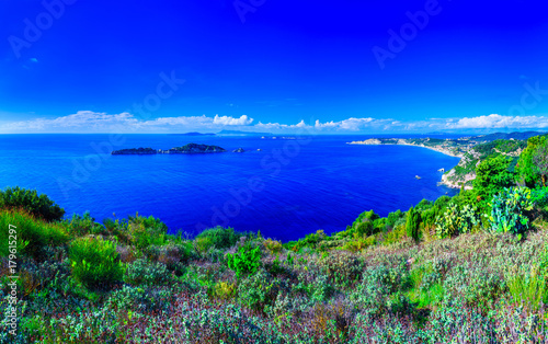 Leinwanddruck Bild Beautiful summertime panoramic seascape. View of the cliff into the crystal clear azure sea bay and distant islands. Agios Stefanos cape. Afionas. Corfu. Greece.