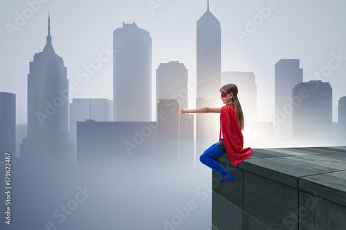 Poster Young girl in superhero costume overlooking the city