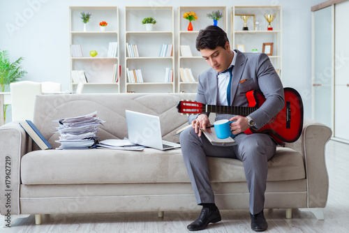 Businessman playing guitar at home Poster