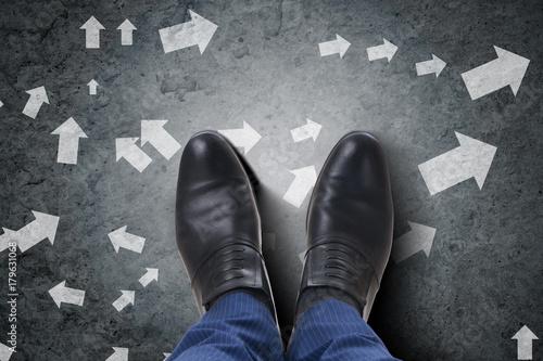 Businessman feet facing difficult choice dilemma
