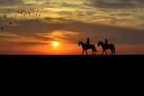 A couple on a horse riders at sunset - 179654489