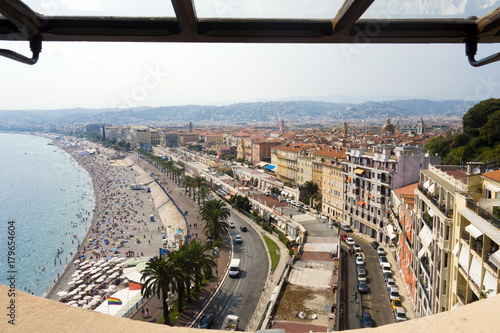 Fotobehang Nice Viewpoint overlooking blue Mediterranean sea beach with palm trees and bright and colorful city of Nice France on sunny day in Cote d'Azure