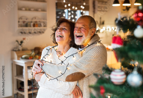Senior couple hugging at home at Christmas time.