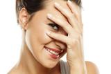Ashamed young woman peeking trough her fingers