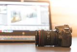 Profi Spiegelreflexkamera auf dem Tisch, Laptop im Hintergrund - 179688412
