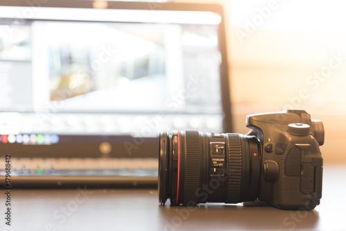Fototapeta Profi Spiegelreflexkamera auf dem Tisch, Laptop im Hintergrund