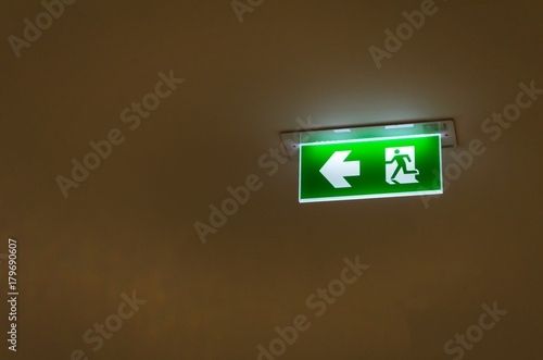 green emergency fire exit sign on ceiling in office building or shopping mall Poster