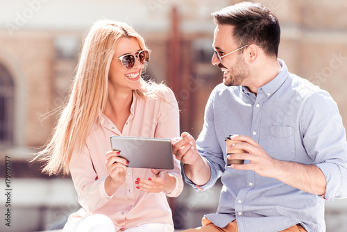 Couple using a tablet and cafe to go outdoor.