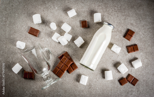 Foto op Canvas Chocolade Christmas hot drinks recipes, Set of ingredients for hot chocolate: milk bottle, chocolate, marshmallow. Gray stone background, copy space top view