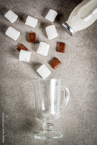 Tuinposter Chocolade Christmas hot drinks recipes, Set of ingredients for hot chocolate: milk bottle, chocolate, marshmallow. Gray stone background, copy space top view