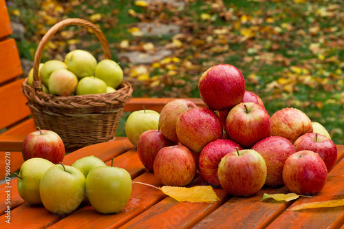 Foto op Plexiglas Gras Red Apples with Basket on the Garden Table