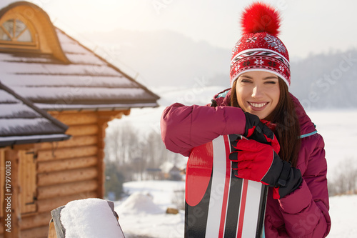 obraz lub plakat winter, leisure, sport and people concept - happy young woman in red hat outdoors
