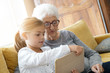 Little girl with grandmother using tablet at home
