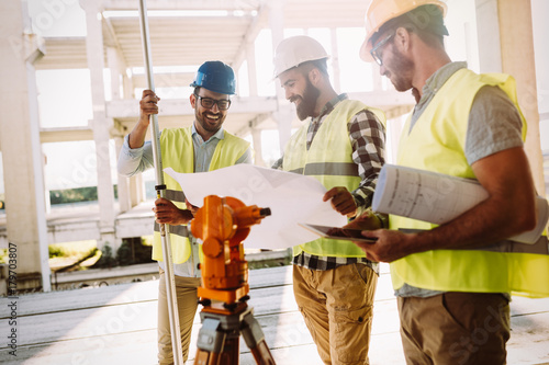 Portrait of construction engineers working on building site - 179703807