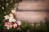Christmas background with green fir branches, gold fir cones and an angel toy on a wooden surface. Flat lay with copy space. - 179706683