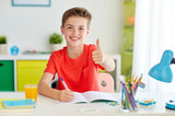 happy student boy writing to notebook at home