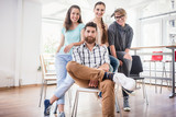 four co-workers wearing casual clothes during work in a modern hub for freelancers - 179720432