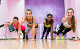 Fototapety Happy women showing thumbs up from plank position as a like sign for a trendy fitness club