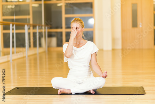 Woman sitting and practicing yoga in studio Poster