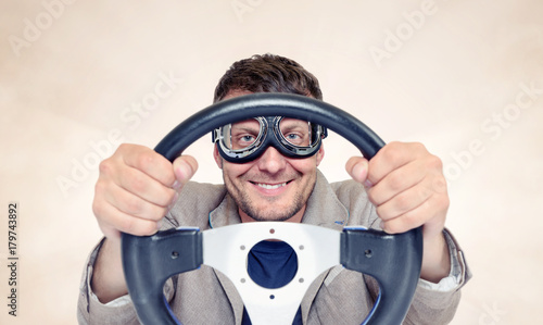 Bearded happy man in stylish goggles with steering wheel on background, car driver concept