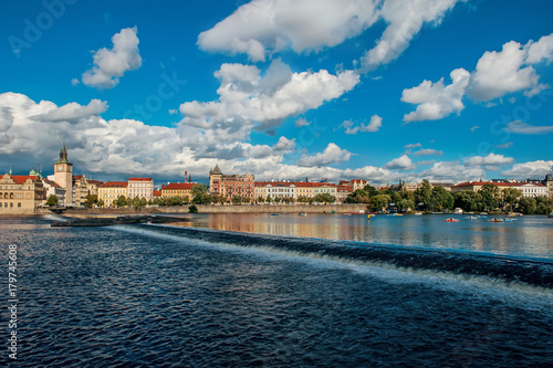 Beautiful view from the river Vltava on the Bank of Prague on a Sunny day with a dramatic sky Poster