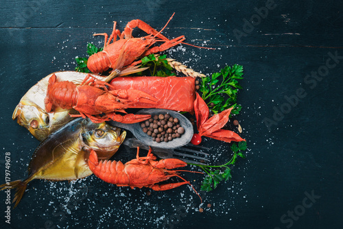 Fridge magnet Seafood. Fish Vomer, lobster, salmon. On a wooden background. Top view. Free space for text.