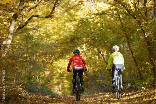 Poster Outdoor sport. Rear view full length shot of two female cyclists riding a trail.