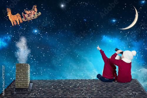 Merry Christmas and happy holidays!Two little brothers sitting on the roof and looking at Santa Claus flying in his sleigh against moon sky. Kids enjoy the holiday. Christmas legend concept.