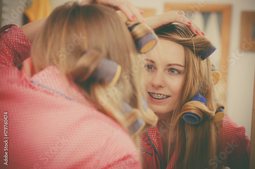 Foto op Canvas Kapsalon Woman curling her hair using rollers