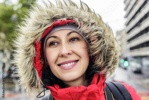 Attractive smiling woman in jacket with fur hood. Plakát